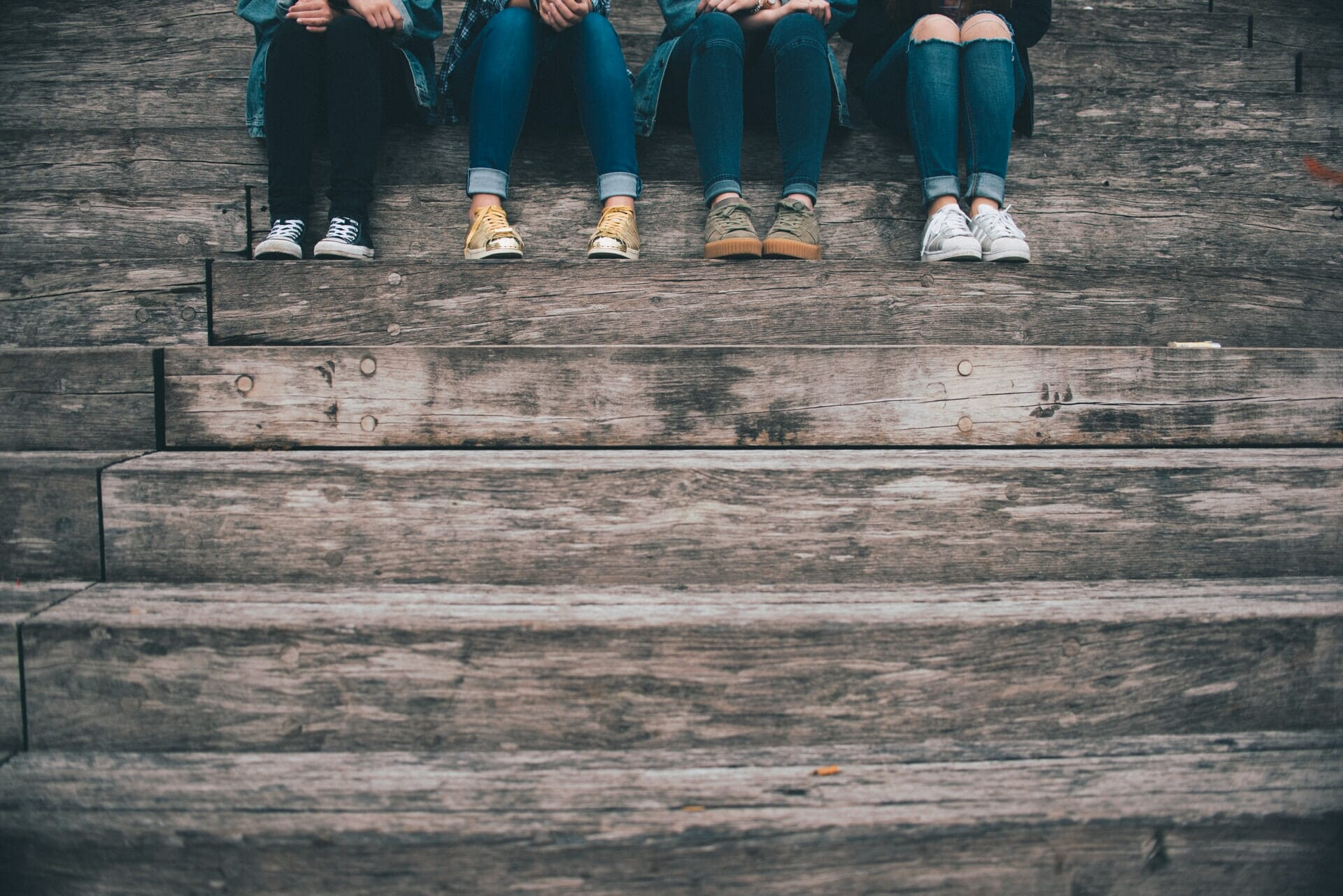 Group of 4 people sitting on stairs.