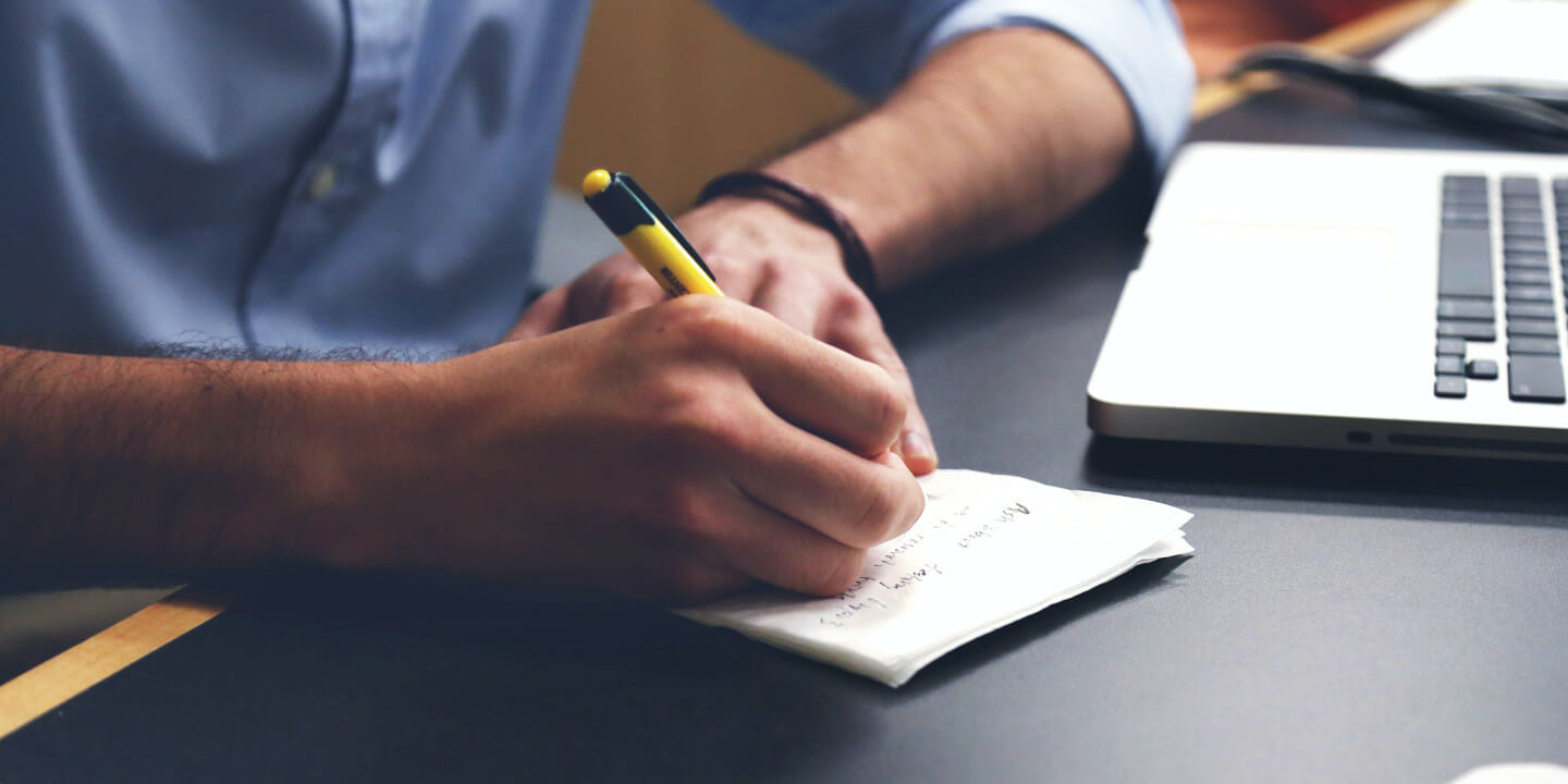 Man writing on paper at desk.