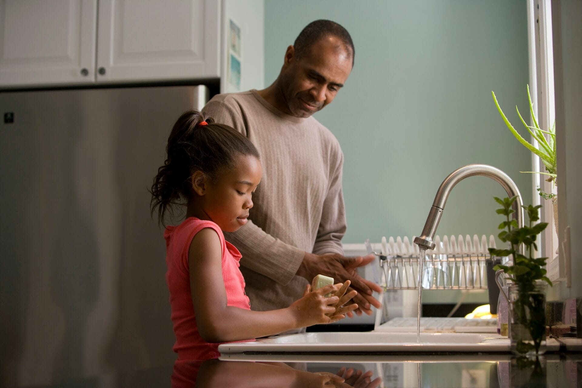 Father and daughter washing hands at kitchen sink.