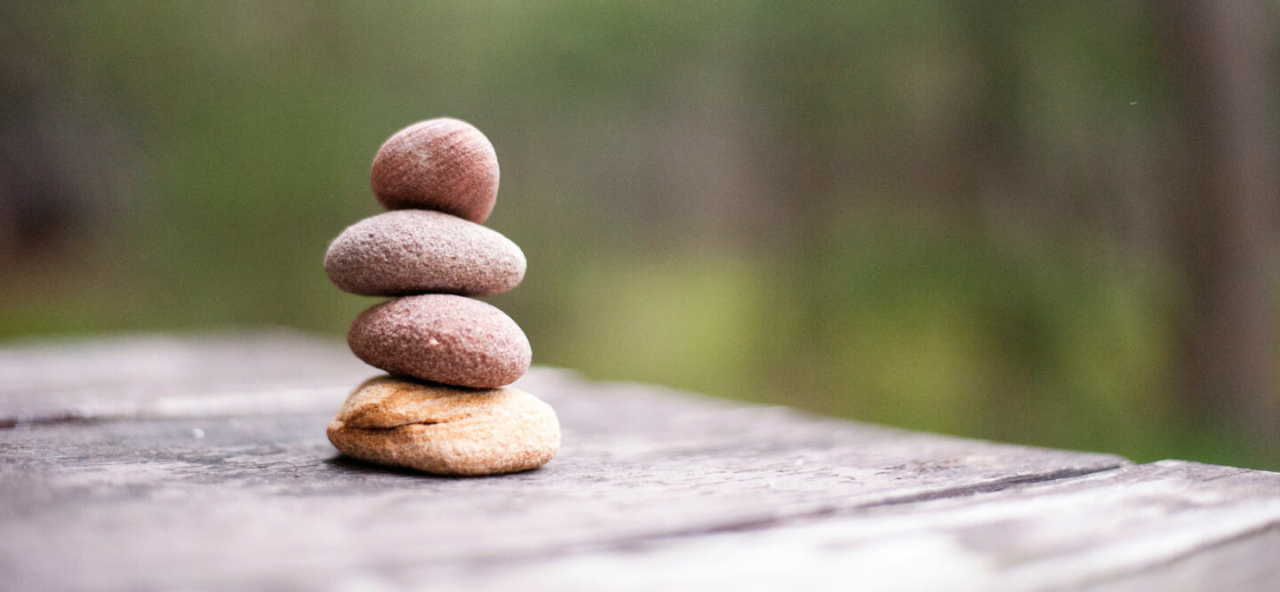 Stack of four rocks on wooden table.