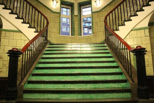 Green staircase with brown railing.