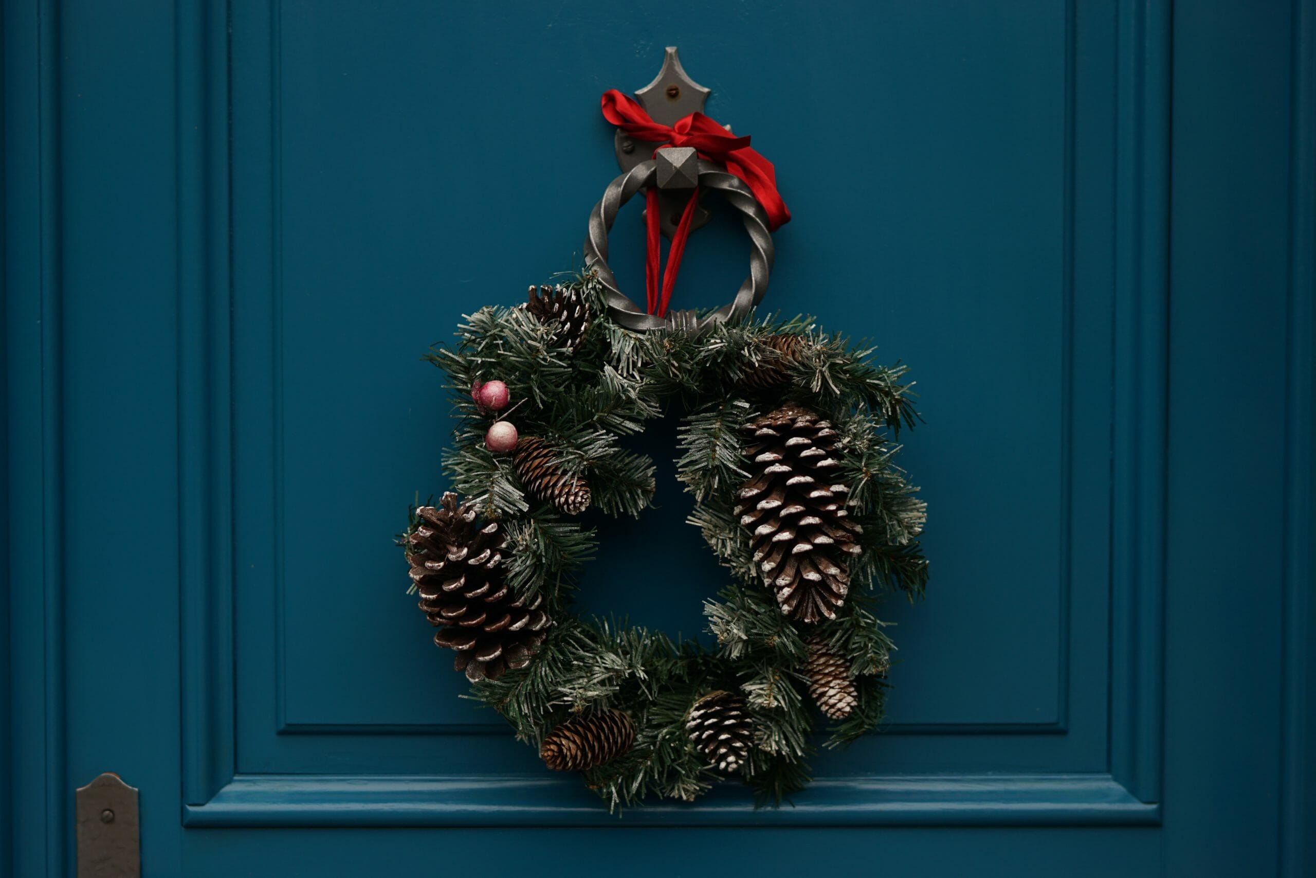 A Christmas wreath hanging on a teal door.
