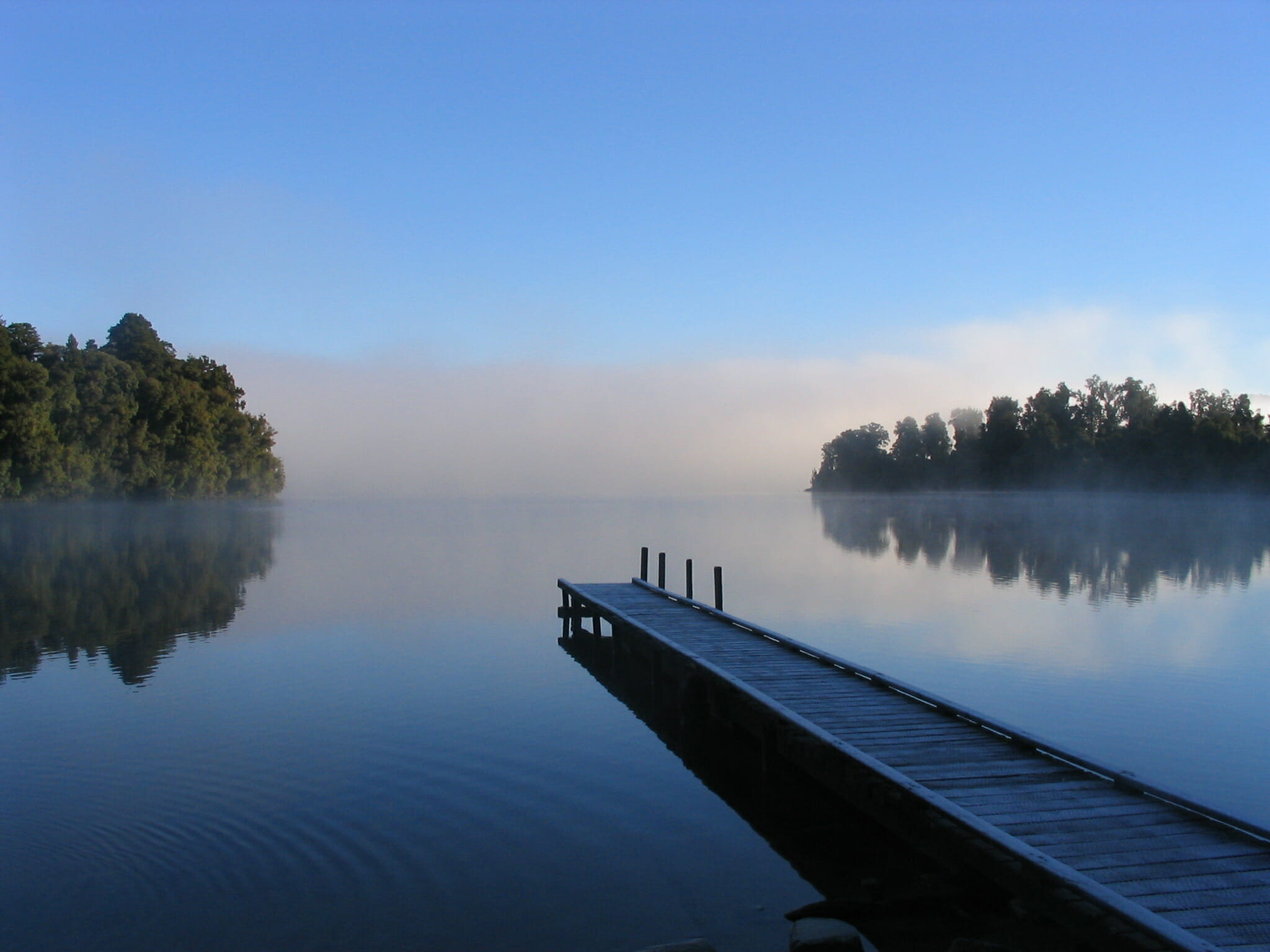 Dock on lake with trees on either side.