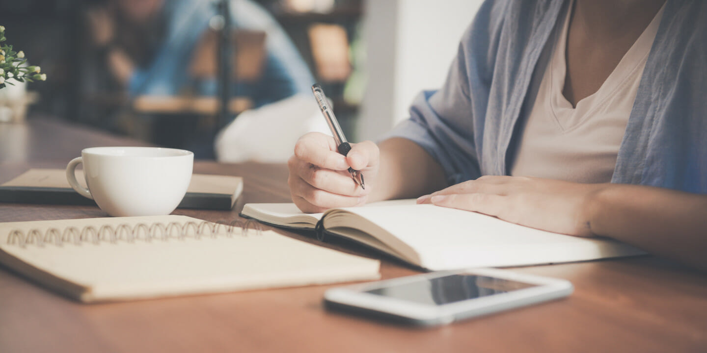 Person sitting a table with coffee, journal, phone and holding a pen writing.
