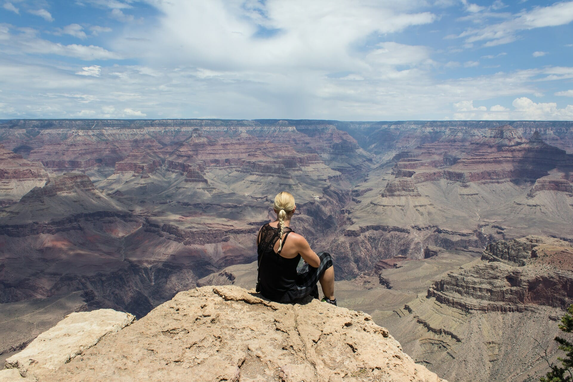 Woman sitting and looking out over the Grand Canyon.