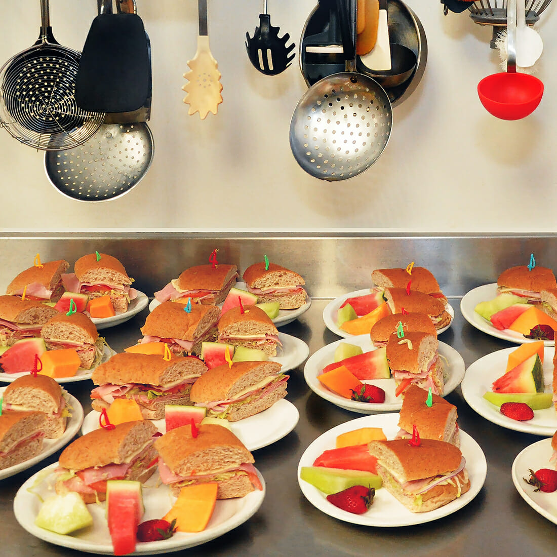 Sandwiches and fruit on plates in the Punanai Centre kitchen.