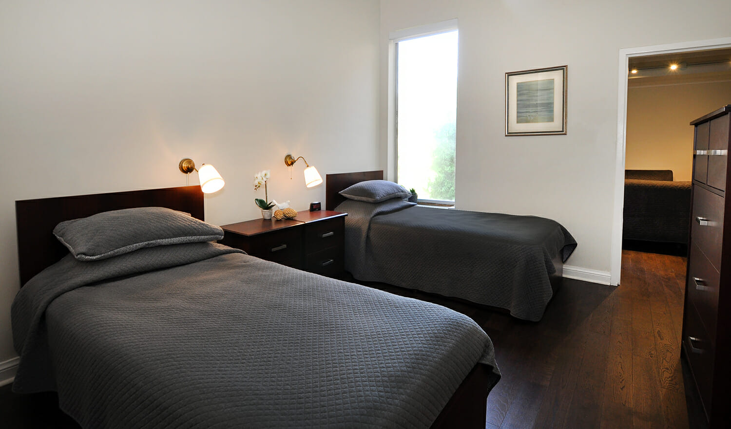 Two beds with grey bedding in Munro Centre bedroom.