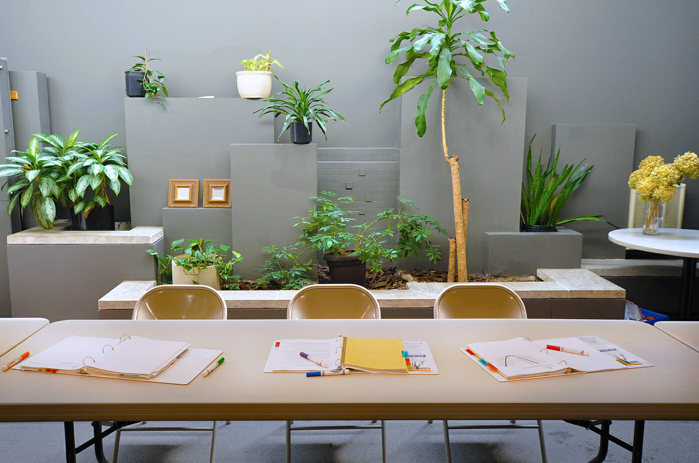 Table and chairs with binders and markers, in front of wall with plants at the Wright Centre.