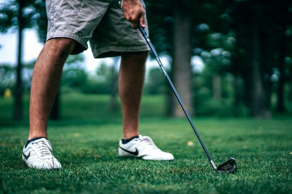 Person standing on golf course with golf club.