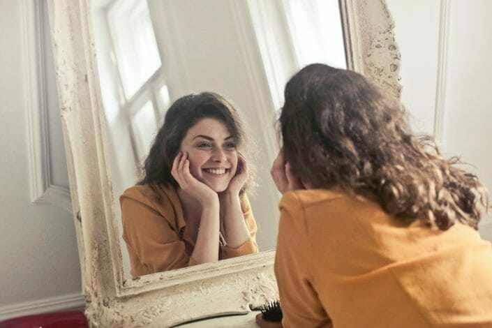 Woman in recovery looking in mirror and smiling.