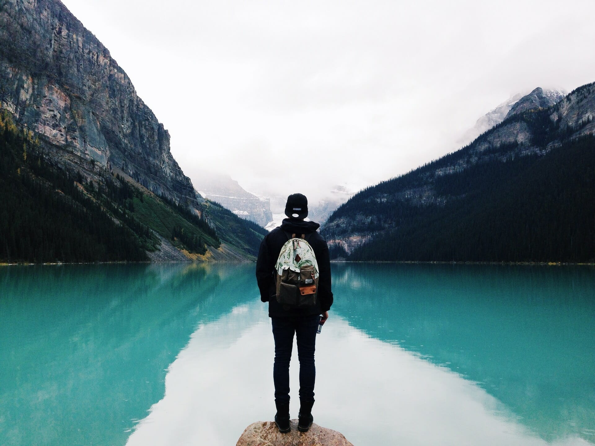 Man standing by lake with mountains in the distance.