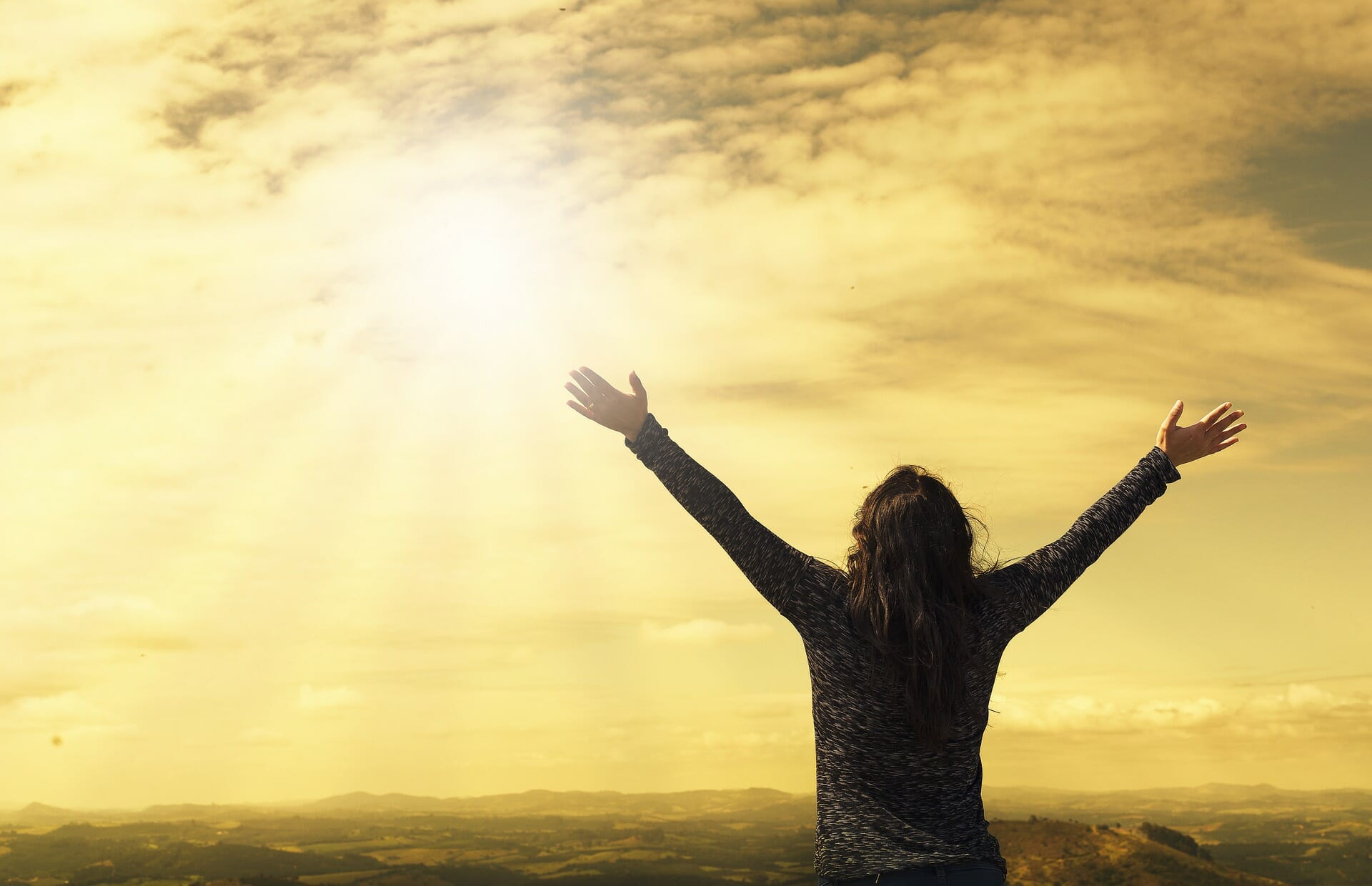 Person holding their arms up in the air and looking towards a sun filled sky.