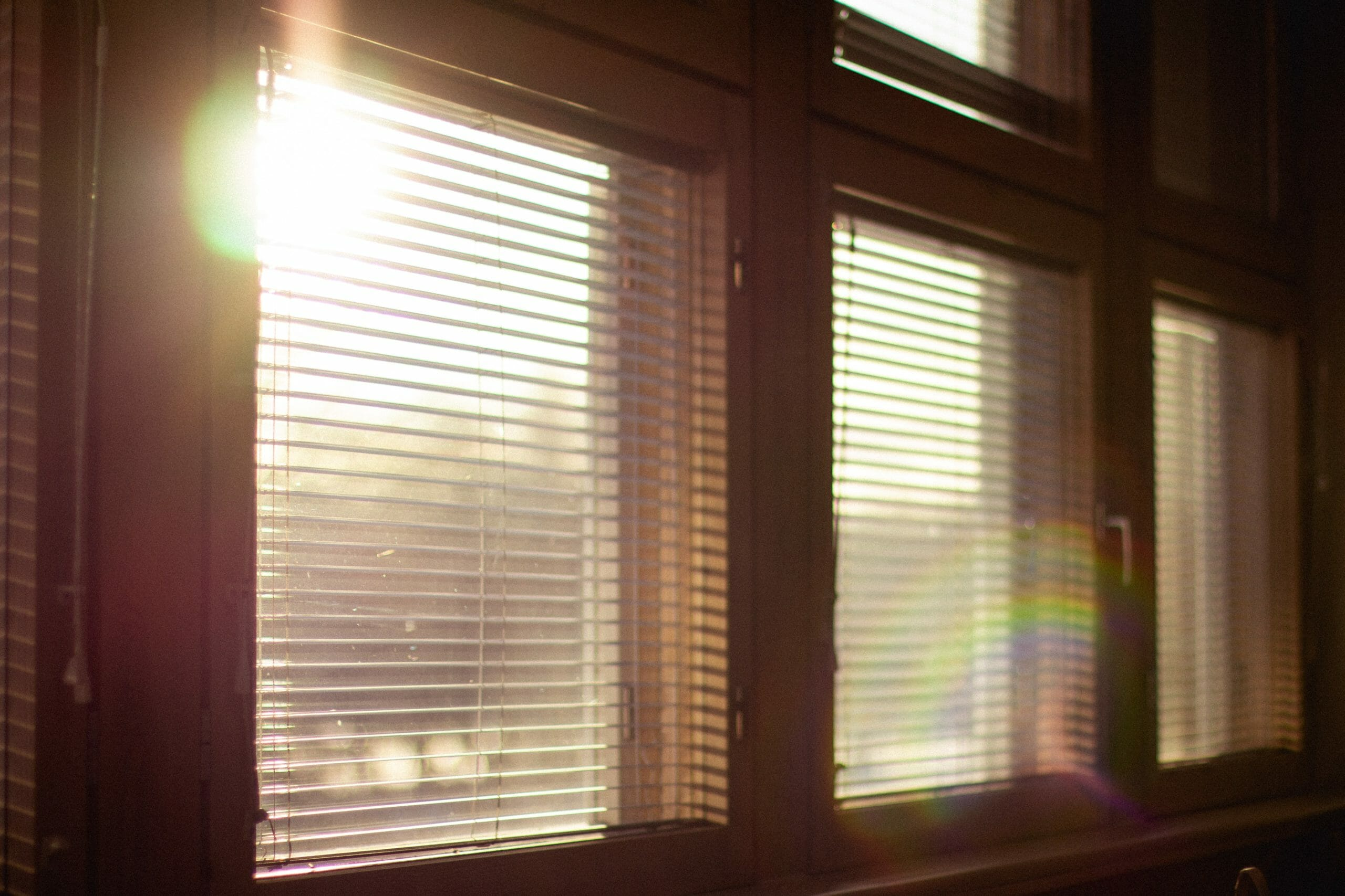 Window blinds with sun shining in.