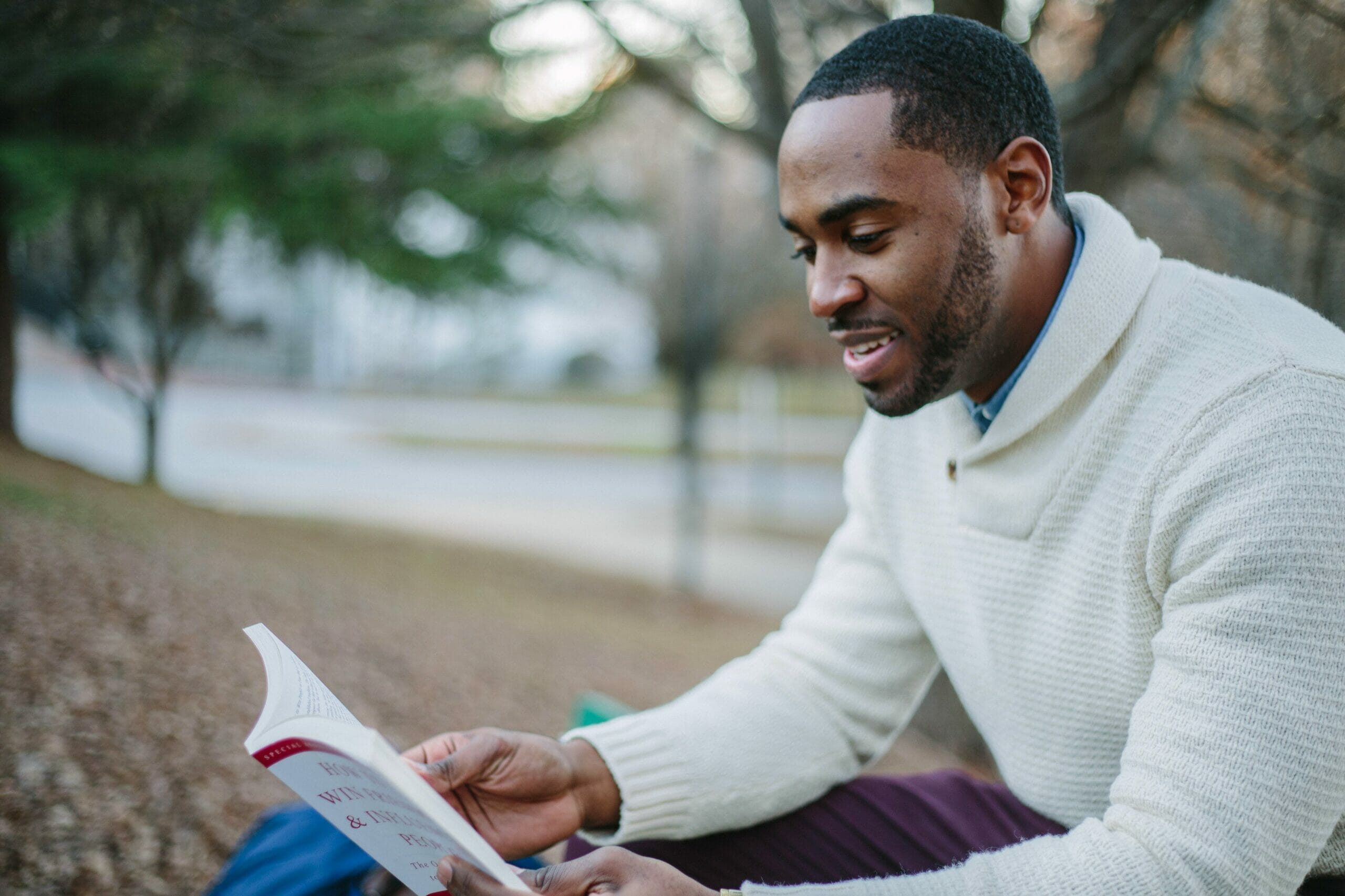 Man sitting on bench and reading a book.