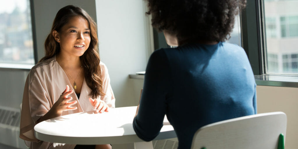 two diverse women sitting across table from one another in a counselling session