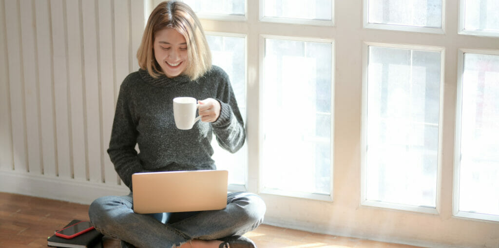 happy women on computer at home after completing heroin addiction rehab