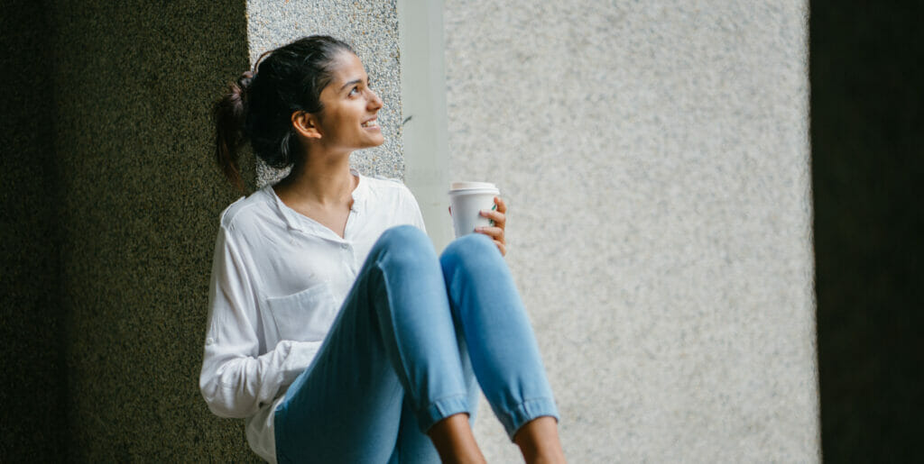 Woman sitting near window holding a cup of coffee.