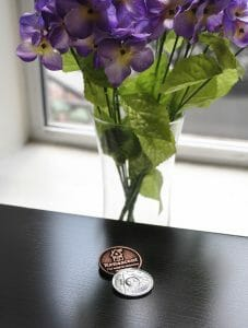 renascent addiction treatment centre medallion for recovery from addiction with bouquet of flowers