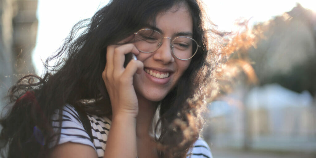 Young woman wearing glasses, smiling and talking on phone.