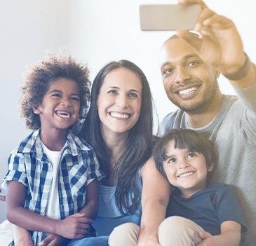 Family of four taking a selfie family photo.