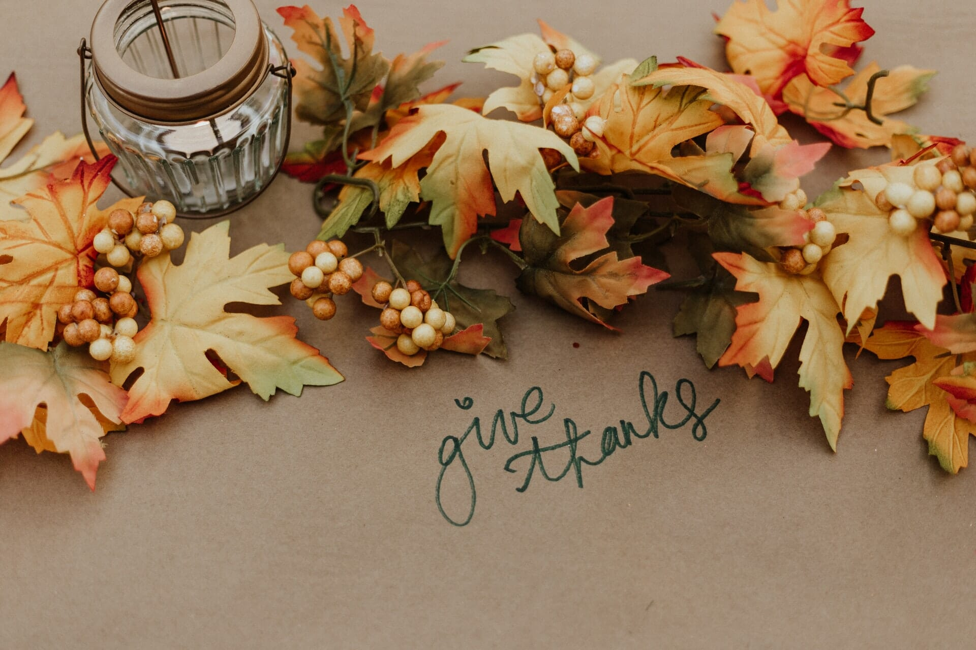 Fall leaves and candle holder on brown paper that says give thanks.