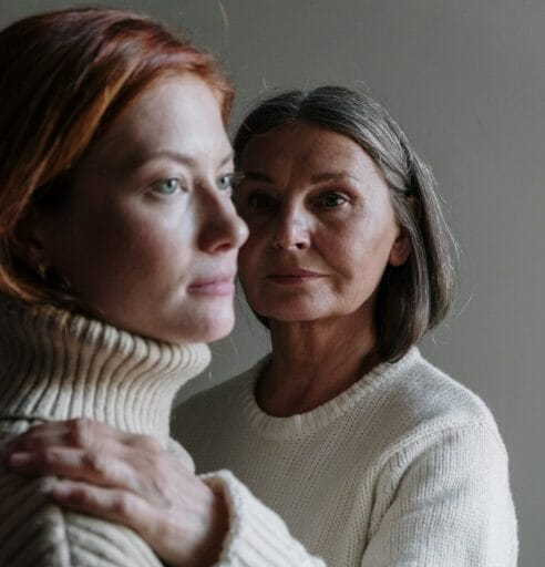 One woman looking at another woman and holding her shoulder.