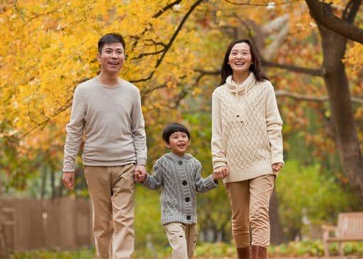 Family of three walking hand in hand.