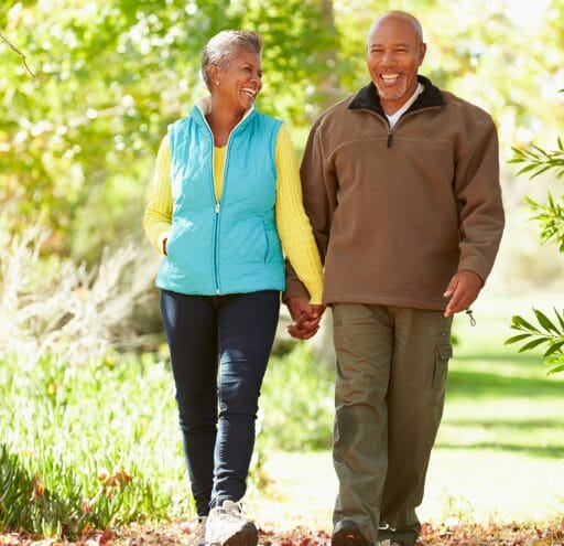 Couple walking on tree lined path holding hands and smiling.